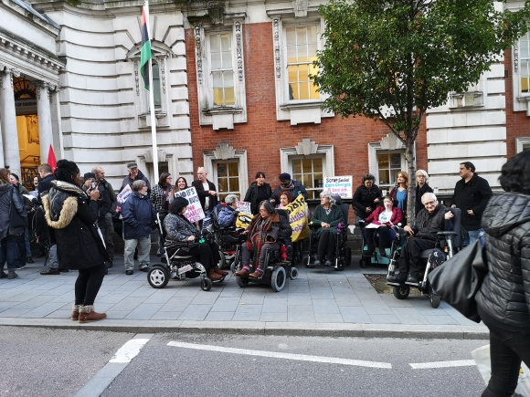 Group of people on a pavement, some in wheelchairs, some carrying banners and placards