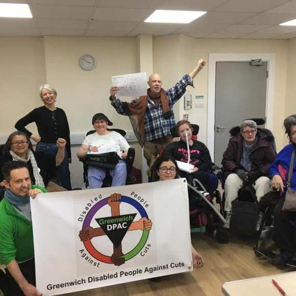 9 people in group photo, 5 wheelchair users, 6 women, 3 men, all Caucasian one East Asian, 2 kneeling up front holding banner 'Greenwich Disabled People Against Cuts ' logo